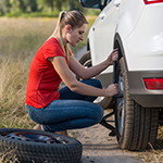 A woman changing a tire